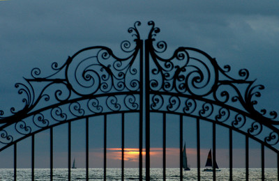 Silhouettes of fancy iron gates (Natatorium) and distant sailboats off the Waikiki coastline as the golden yellow sun peaks through the clouds at sunset  Honolulu, Oahu, Hawaii