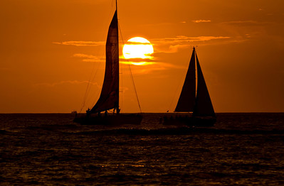 Silhouettes of sailboats can be seen returning to the Ala Wai Harbor in Waikiki at sunset