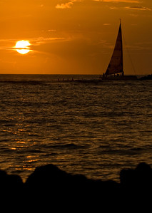 Silhouettes of sailboat as they head for the harbor at sunset  Waikiki, Hawai'i