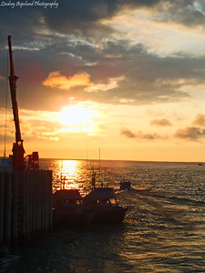 A sunset at Pederson Point, Alaska, looking at a drift gillnet vessels and a set gillnet skiff at the North Pacific Seafoods dock