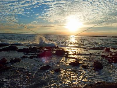 Beach sunset with a wave crashing.