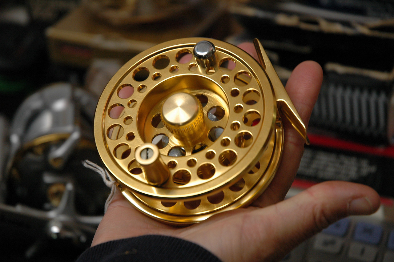 Fly reel awaiting line, lure and one mad salmon on the other end