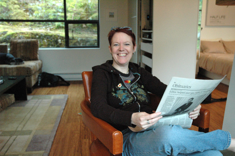 The webmaster, Laurie, enjoying a toasty fire, gorgeous views and the Saturday national paper