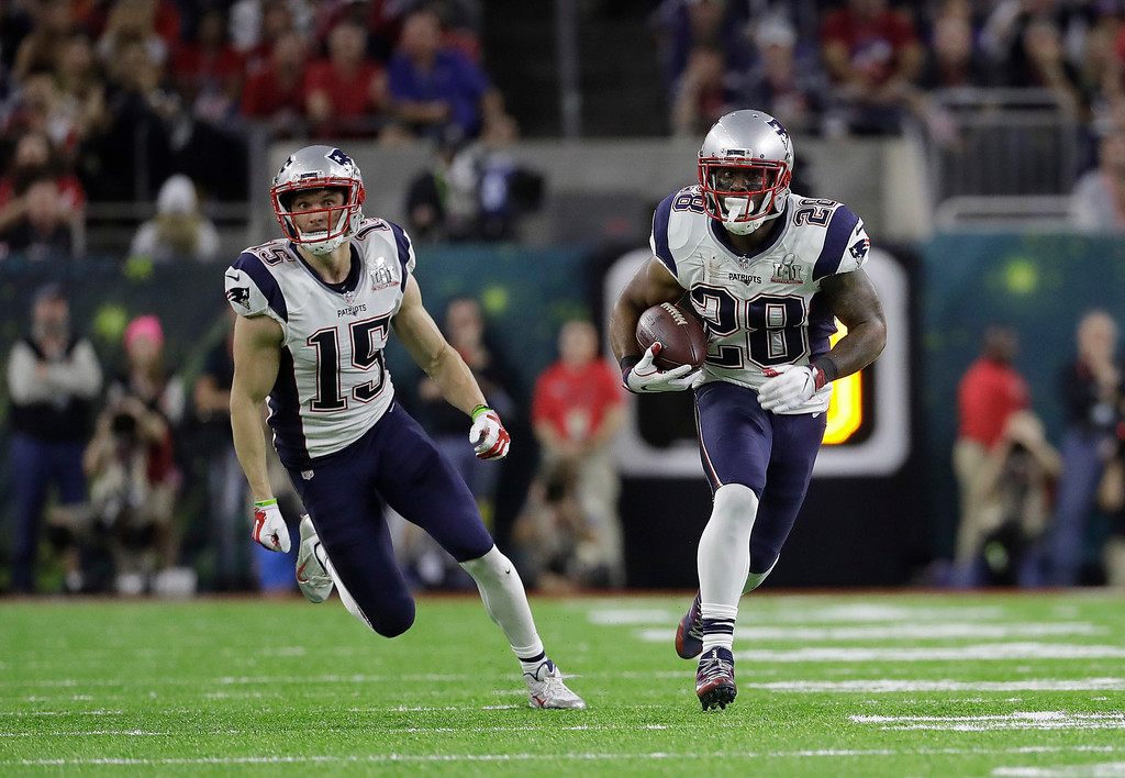 . New England Patriots\' James White, right, runs in front of Chris Hogan during the first half of the NFL Super Bowl 51 football game against the Atlanta Falcons Sunday, Feb. 5, 2017, in Houston. (AP Photo/Chuck Burton)
