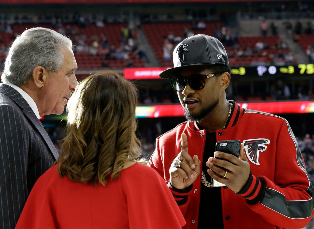 . Usher, right, talks to Atlanta Falcons owner Arthur Blank before the NFL Super Bowl 51 football game between the Atlanta Falcons and the New England Patriots Sunday, Feb. 5, 2017, in Houston. (AP Photo/David J. Phillip)