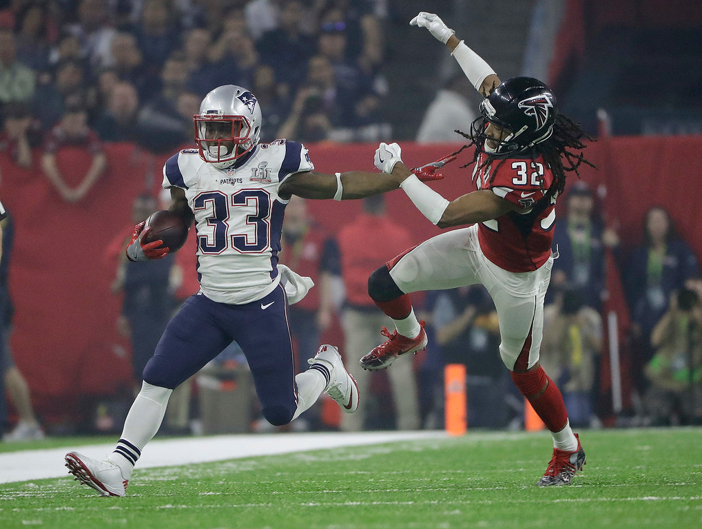 . New England Patriots\' Dion Lewis, left, runs against Atlanta Falcons\' Jalen Collins during the second half of the NFL Super Bowl 51 football game Sunday, Feb. 5, 2017, in Houston. (AP Photo/Elise Amendola)