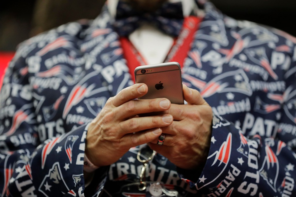 . New England Patriots fan Jason Woolley, of Murrieta, Calif., looks at his phone before the NFL Super Bowl 51 football game between the Patriots and the Atlanta Falcons, Sunday, Feb. 5, 2017, in Houston. (AP Photo/Jae C. Hong)
