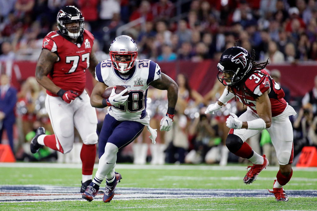 . New England Patriots\' James White carries past Atlanta Falcons\' Jalen Collins, right, and Ra\'Shede Hageman, left, in the first half of the NFL Super Bowl 51 football game Sunday, Feb. 5, 2017, in Houston. (AP Photo/Patrick Semansky)