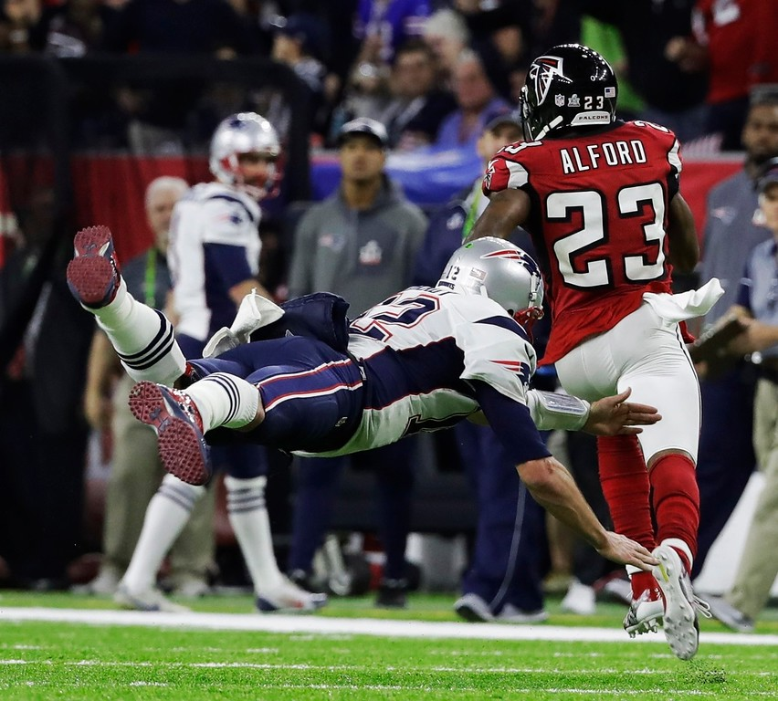 . New England Patriots\' Tom Brady (12) dives toward Atlanta Falcons\' Robert Alford as Alford runs the ball to the end zone for a touchdown after intercepting a pass during the first half of the NFL Super Bowl 51 football game Sunday, Feb. 5, 2017, in Houston. (AP Photo/Chuck Burton)