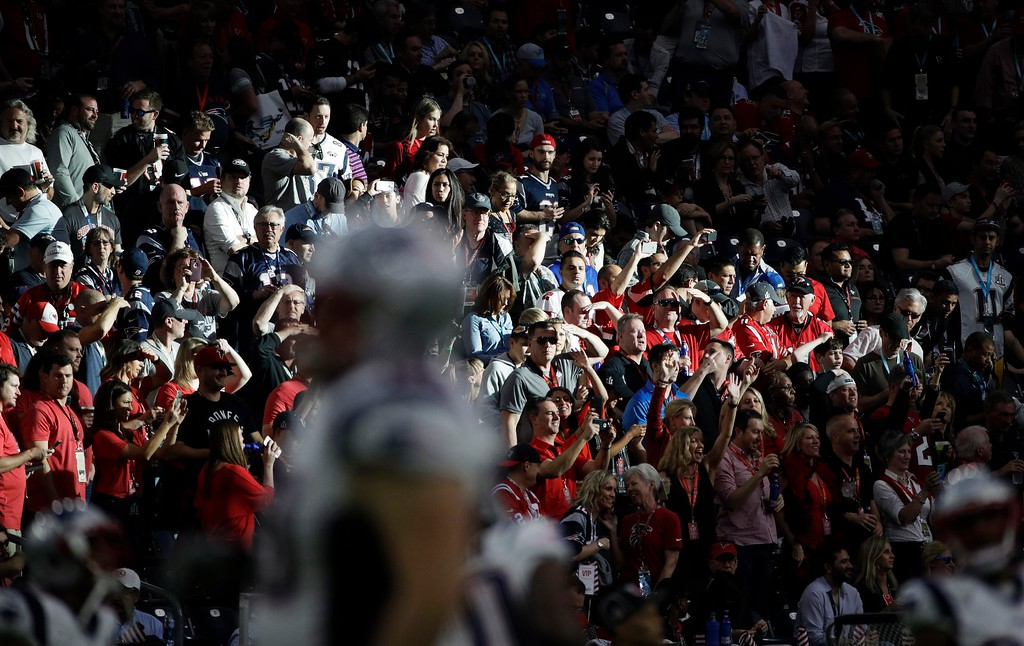 . Fans watch as the New England Patriots warm up before the NFL Super Bowl 51 football game against the Atlanta Falcons, Sunday, Feb. 5, 2017, in Houston. (AP Photo/Jae C. Hong)
