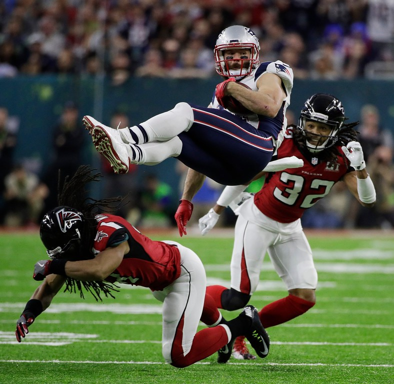 . New England Patriots\' Julian Edelman is upended by Atlanta Falcons\' Philip Wheeler, bottom, during the first half of the NFL Super Bowl 51 football game Sunday, Feb. 5, 2017, in Houston. (AP Photo/Jae C. Hong)