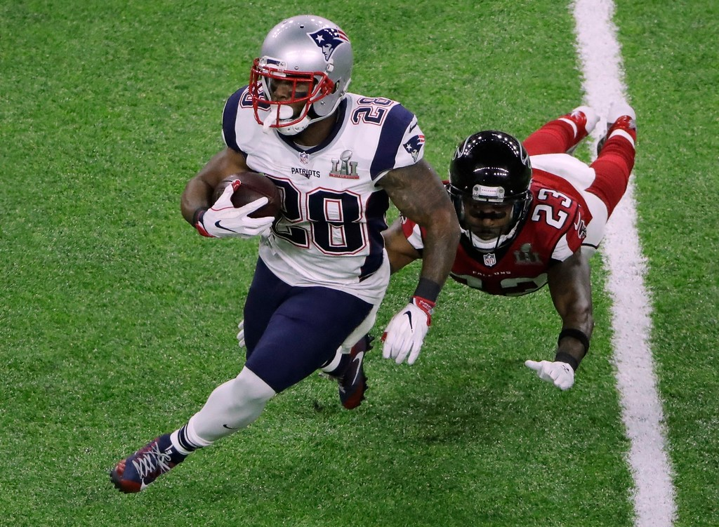 . New England Patriots\' James White, left, breaks a way from Atlanta Falcons\' Robert Alford during the first half of the NFL Super Bowl 51 football game Sunday, Feb. 5, 2017, in Houston. (AP Photo/Charlie Riedel)