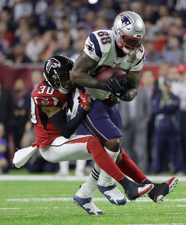 . New England Patriots\' Martellus Bennett, right, is tackled by Atlanta Falcons\' Deji Olatoye during the first half of the NFL Super Bowl 51 football game Sunday, Feb. 5, 2017, in Houston. (AP Photo/Chuck Burton)