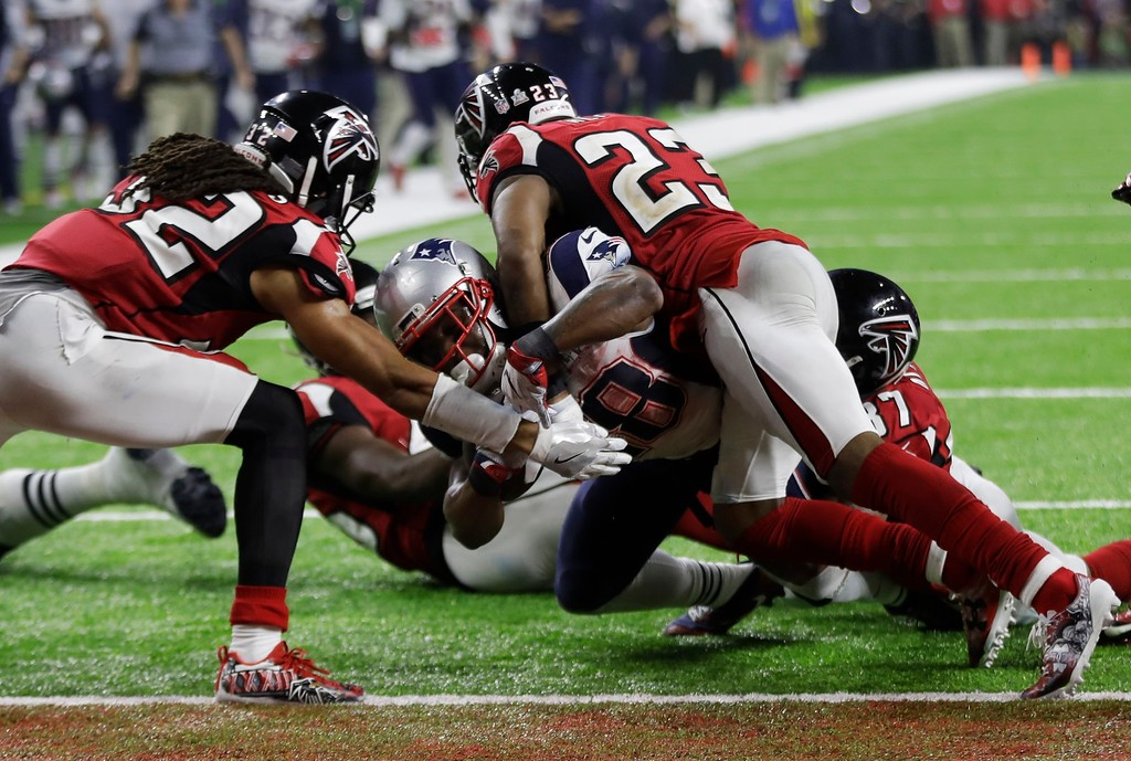 . New England Patriots\' James White scores the winning touchdown between Atlanta Falcons\' Jalen Collins, left, and Robert Alford during overtime of the NFL Super Bowl 51 football game Sunday, Feb. 5, 2017, in Houston. (AP Photo/Elise Amendola)