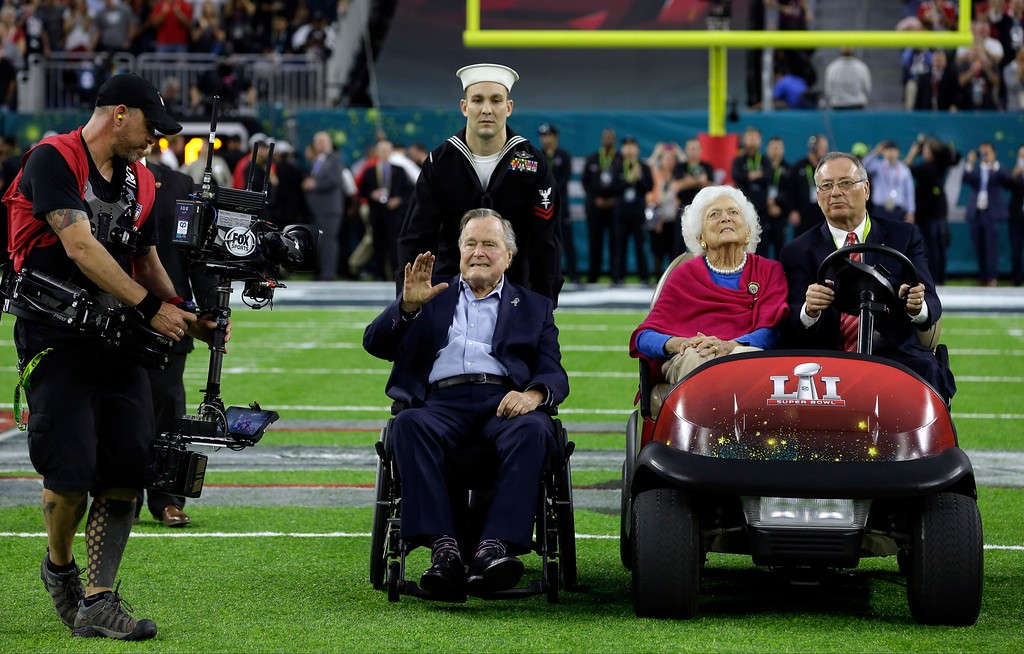 . Former President George H.W. Bush and wife, Barbara wave as they arrive on the field for a coin toss before the NFL Super Bowl 51 football game between the Atlanta Falcons and the New England Patriots Sunday, Feb. 5, 2017, in Houston. (AP Photo/David J. Phillip)