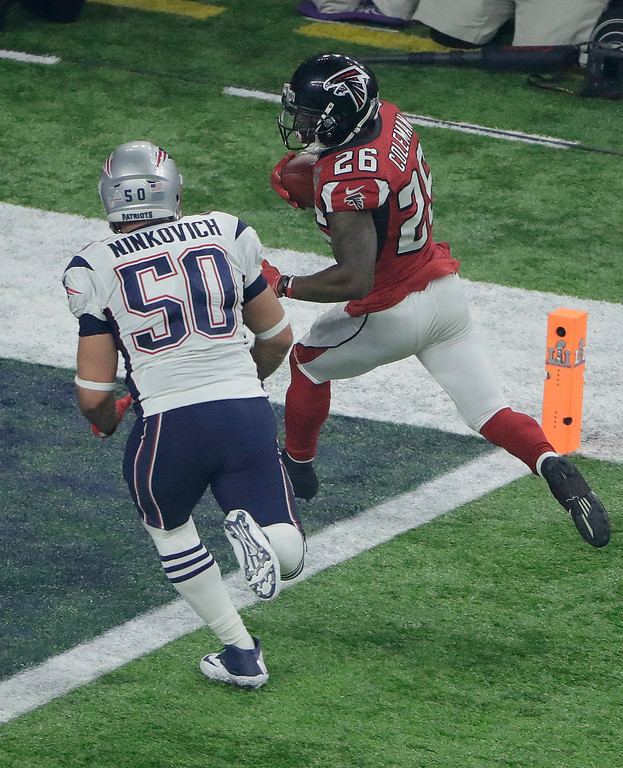 . Atlanta Falcons\' Tevin Coleman, right, scores past New England Patriots\' Rob Ninkovich during the second half of the NFL Super Bowl 51 football game Sunday, Feb. 5, 2017, in Houston. (AP Photo/Charlie Riedel)