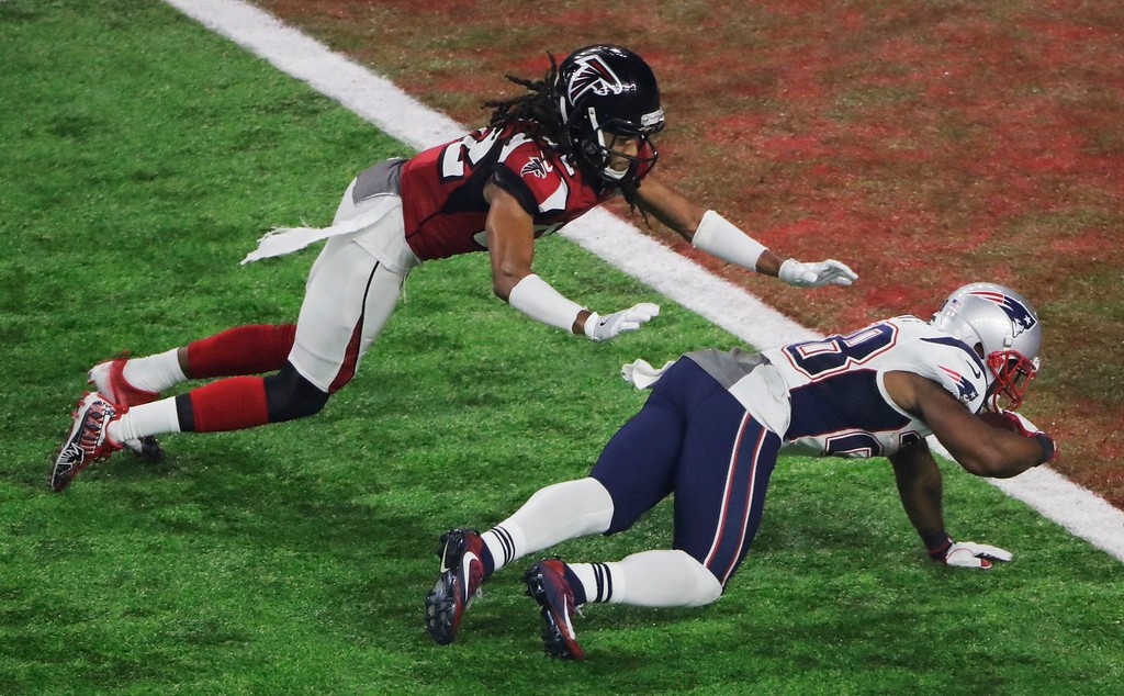 . New England Patriots\' James White scores ahead of Atlanta Falcons\' Jalen Collins during the second half of the NFL Super Bowl 51 football game Sunday, Feb. 5, 2017, in Houston. (AP Photo/Charlie Riedel)