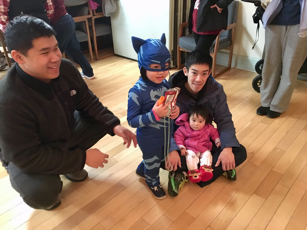 . Justin Chin (left) is pictured with Mark Liu (far right), baby Rachel Lui and Madison Chin, who is dressed like a super hero. Photo by Mary Leach