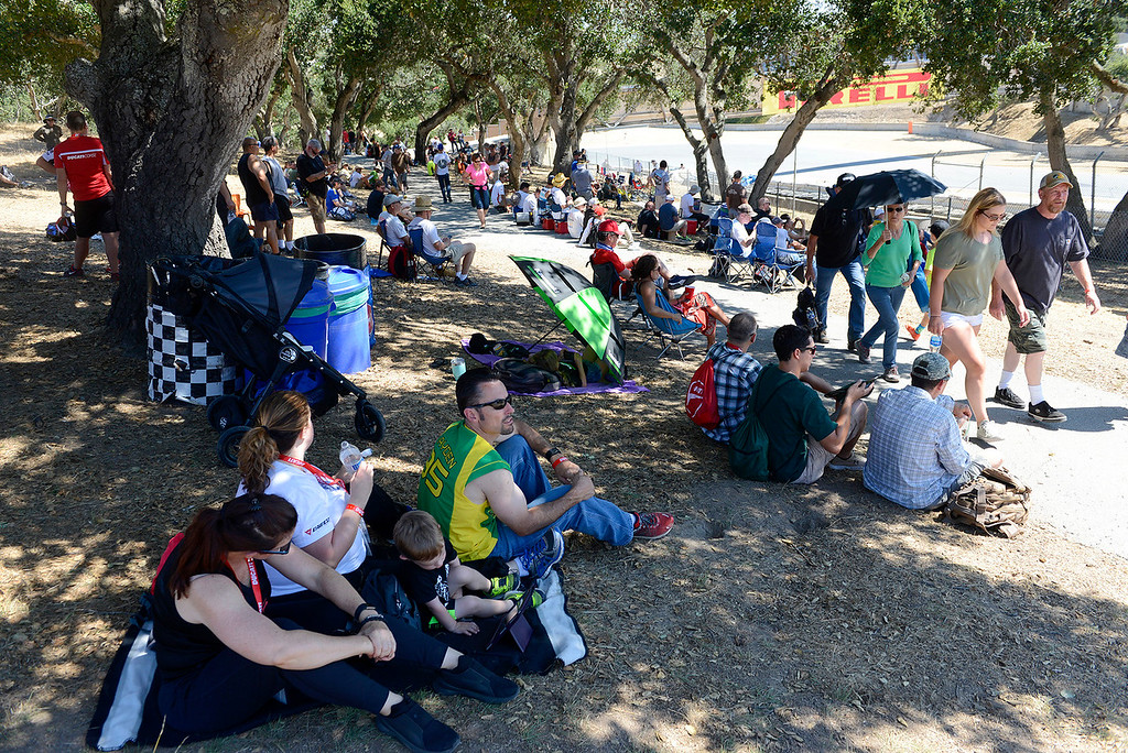 . Fans take cover from the heat at the corkscrew during a practice session at the FIM Superbike World Championship at Mazda Raceway Laguna Seca on Saturday, July 8, 2017.  (Vern Fisher - Monterey Herald)