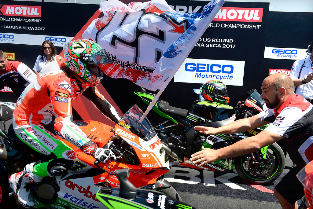 . Chaz Davies (7) rides into victory lane on his Ducati carrying a Nicky Hayden #69 flag after winning the FIM Superbike World Championship race at Mazda Raceway Laguna Seca on Saturday, July 8, 2017.  (Vern Fisher - Monterey Herald)