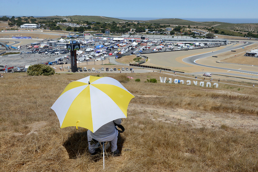 . Tom Jost from San Jose watches the action from underneath his umbrella during a practice session at the FIM Superbike World Championship at Mazda Raceway Laguna Seca on Saturday, July 8, 2017.  (Vern Fisher - Monterey Herald)