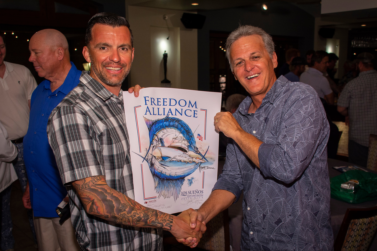 Marine Jason is given a signed print of the custom design by Marine Wildlife Artist Steve Goione.
