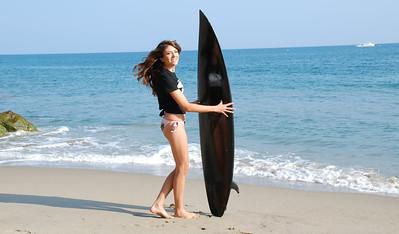 Pretty Bikini Swimsuit Model with Black Surfboard