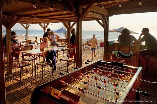 FRANCE. SURF LANDES. LESPRIT SURF DANS LE DEPARTEMENT DES LANDES. Bar/restaurant La Cabane de La Gravière à Hossegor.  C'est l'un des spots phares pour siroter un spritz pieds nus dans le sable en admirant le coucher de soleil. Idéal pour accompagner tapas et burgers proposés par le restaurant.  Café Restaurant