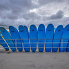 Blue Surfboards Against Fence