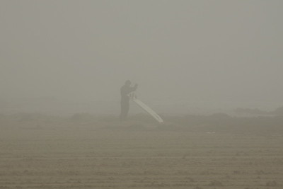 A surfer sorts out his leash ,but can escape the grip of the fog.