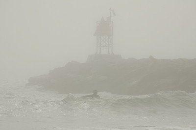 A brave surfer rides the current along the jetty to catch a few swells that roll in out of the fog.