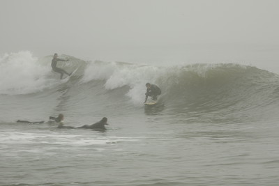 Which two surfers are getting the bigger rush in this shot?