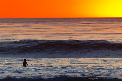 a surfer awaits the perfect ride to end his day