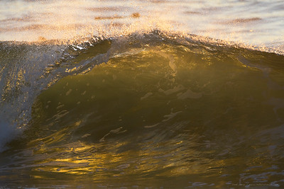 Last light through a breaking wave illuminates colors and surf foam patterns.