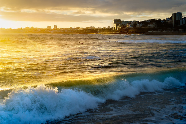 Setting sun, falling on  surfers, with city backdrop. Estoril, Portugal.