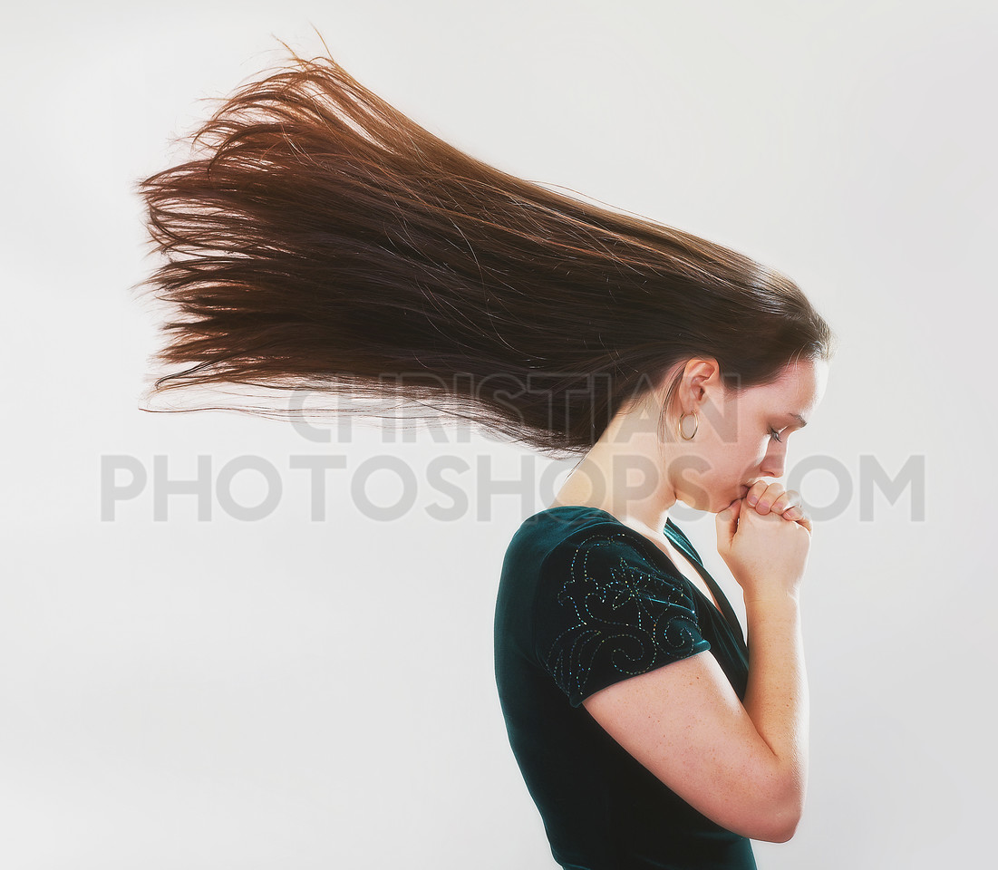 Woman praying with flying hair.