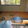 Progress. This flooring was purchased back in 1998, but then I had my motorcycle accident in January 1999 and this project got put on hold until my wifey said get 'er done. This is the old Pergo, before they went with snap lock. So it was important to have straps to pull the boards together as they were glued. Only it has been so long since Pergo switched to snap lock I couldn't rent the straps and had to come up with the jury rigged setup you see on the left.