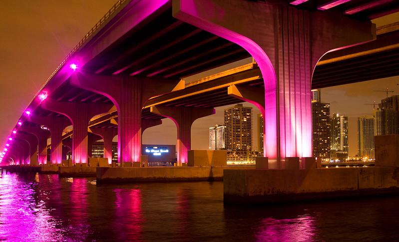 Miami skyline at night from causeway bridges with fishermen