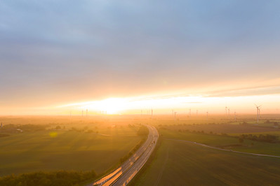 Wind power is generated next to a highway in the open farmland of Uckermark, northern Germany