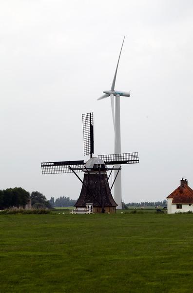 Old Dutch windmill alongside a modern wind turbine in Friesland, Netherlands