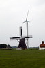 Old Dutch windmill alongside a modern wind turbine in Friesland, Netherlands