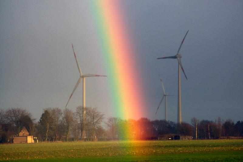 A rainbow forms by wind turbines near Goch, Germany during heavy rain