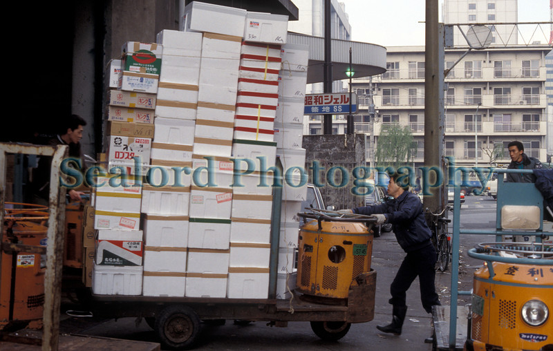 A workman negotiates a three wheel motorized flatbed cart, a taretto, stacked with styrofoam boxes inside a warehouse on the outskirts of the Tsukiji market in Tokyo, Japan.  The taretto is the main form of motorized transport for boxes of fish and produce inside the Tsukiji market.<br /> Photographed in December 1988.<br /> File No. 1288 8<br /> ©RLLord<br /> fishinfo@guernsey.net