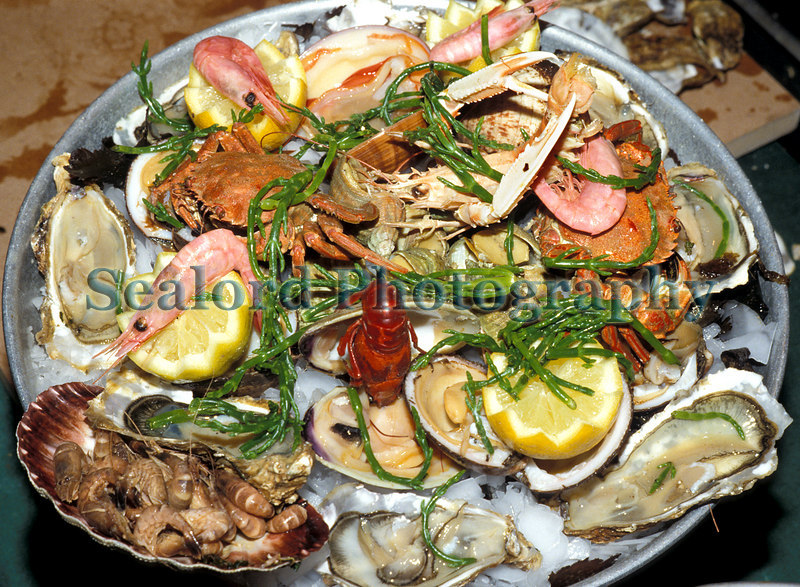 Fruits de mer platter in Brussels, Belgium. Platter includes cupped oysters, Crassostrea sp.; brown shrimp, Crangon crangon; prawns, Pandalus borealis, Procambus freshwater crayfish; velvet swimming crab, Necora puber; whelk, Buccinum undatum; a venus clam, Callista chione; dog cockle or amande de mer, Glycmeris glcycyermis; Dublin bay prawn or scampi, Nephrops norvegicus; and samphire also known as glasswort or Salicornia.<br /> Photographed in August 1988.<br /> File No. 30 0888<br /> ©RLLord<br /> fishinfo@guernsey.net