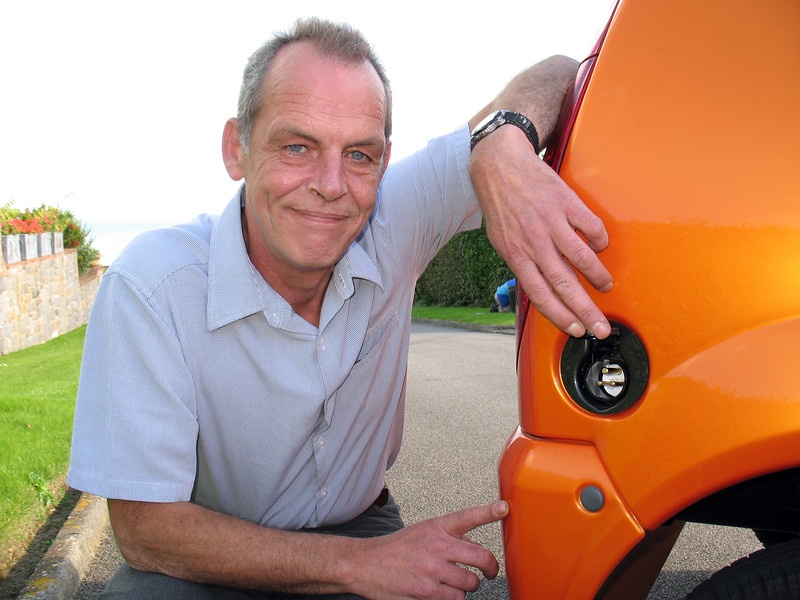 Paul Domaille by the plug-in charge point on his electric Mega City on 29 September 2009