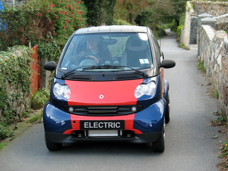 Mark Parr, founder of The Electric Vehicle Company, drives his battery powered Smart Car up a country lane in Guernsey, Channel Islands, Great Britain.  Mark converted the petrol engine Smart Car to an electric vehicle, which costs about one penny per mile to run.  Mark will be installing lithium ion batteries which will give the car an average range of 50 miles on a full charge.  These batteries can be discharged 2000 times to 80 percent of their capacity so they should last as long as the car.<br /> <br /> Mark 's electric Smart car is an ideal solution for short distance commuting and island living.  The car can be charged overnight ready for a full day of trips around Guernsey's 24 square miles.  <br /> <br /> Mark's Electric Vehicle Company can be contacted on +44 (0)1481 264434<br /> <br /> File No. 181007 1387<br /> ©RLLord<br /> fishinfo@guernsey.