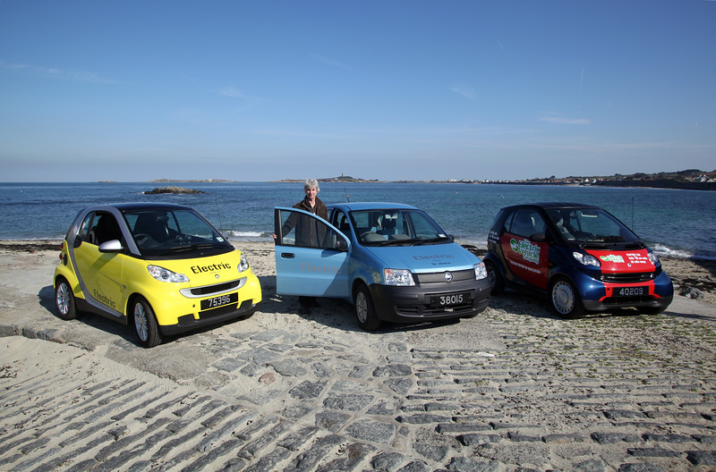 Electrical engineer Mark Parr with three of the cars his company converted to battery power