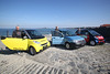 Three electric powered cars converted by The Electric Vehicle Company in Rocquaine Bay, Guernsey stand on the slipway to Fort Grey.  Marine engineer Mark Rive stands by the yellow Smart EV.  Electrical and mechanical engineer Mark Parr stands by the converted Fiat Panda and John Aston stands by the red Smart EV.<br /> File No. 310309 2711<br /> ©RLLord<br /> sustainableguernsey@gmail.com