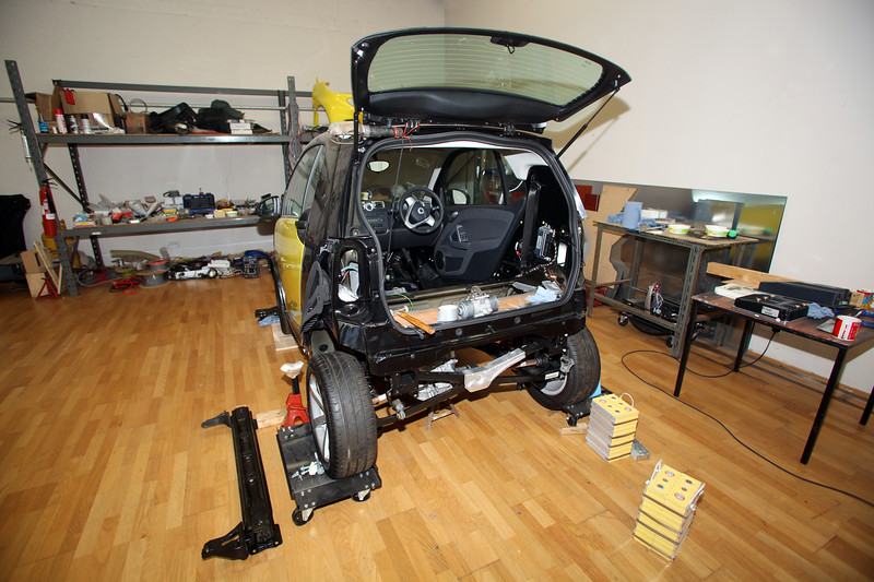 Inside the research & development facility of The Electric Vehicle Company in Guernsey, Channel Islands, Great Britain where petrol-powered cars are converted to battery power.  Here a Smart Car has had the petrol engine removed and it is waiting for the installation of 24 lithium battery cells.<br /> File No. 310309 2688<br /> ©RLLord<br /> sustainableguernsey@gmail.com