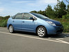 This is an image of the Toyota Prius T3 in Guernsey.  Even if it wasn't a hydrid car, which produces excellent fuel economy, it would still be a fabulous car.  This car has a battery in the boot / trunk which is charged up by the engine and when braking.  The car computer decides whether to power the car with the battery or the petrol engine.  This car is ideal for city driving when the battery is used extensively to power the car.  Besides this car providing a very comfortable driving experience it produces low C02 emissions of about 104 grams per kilometre.  Under typical Guernsey driving conditions (top speed 35 mph, lots of stopping and starting, up & down hills) the Toyota Prius achieves about 55 miles per gallon (mpg).<br /> File name: Toyota Prius Guernsey 100907 778<br /> fishinfo@guernsey.net